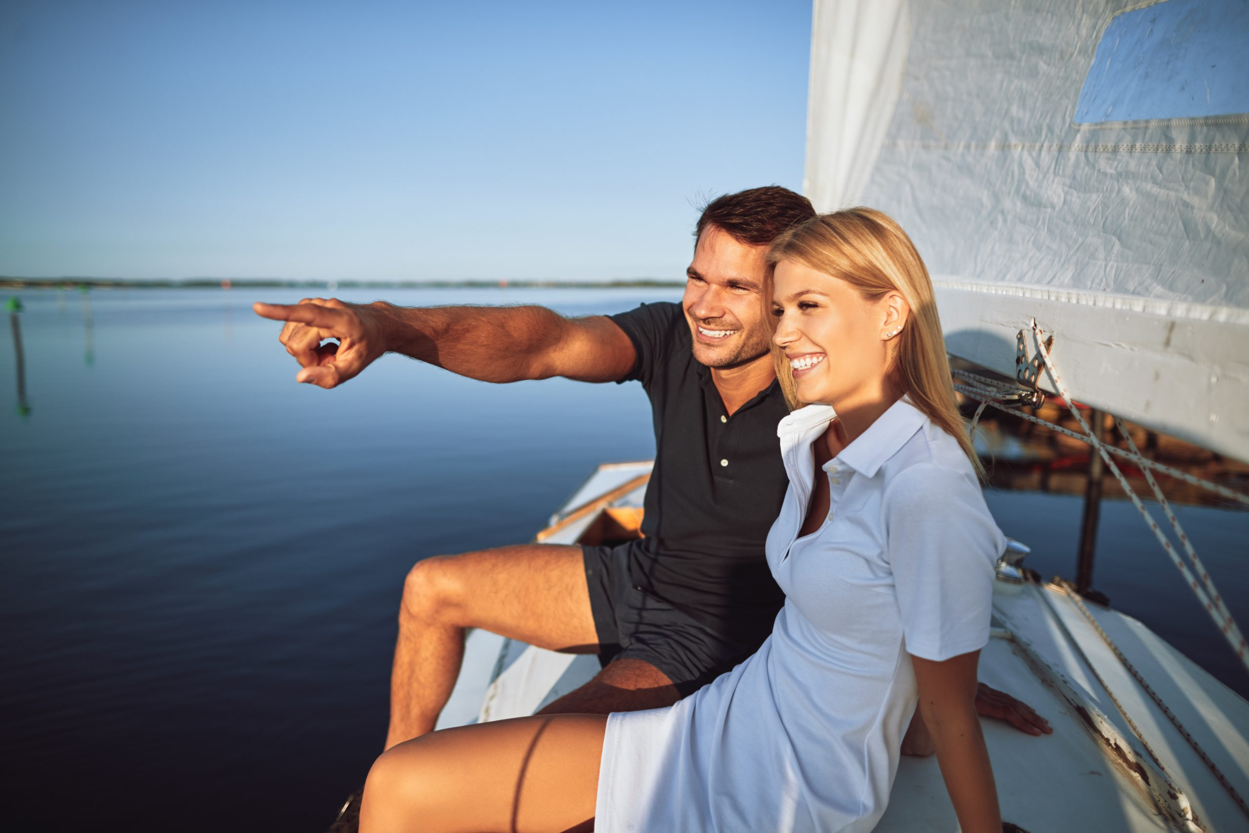 Smiling young couple enjoying the sea views while out sailing