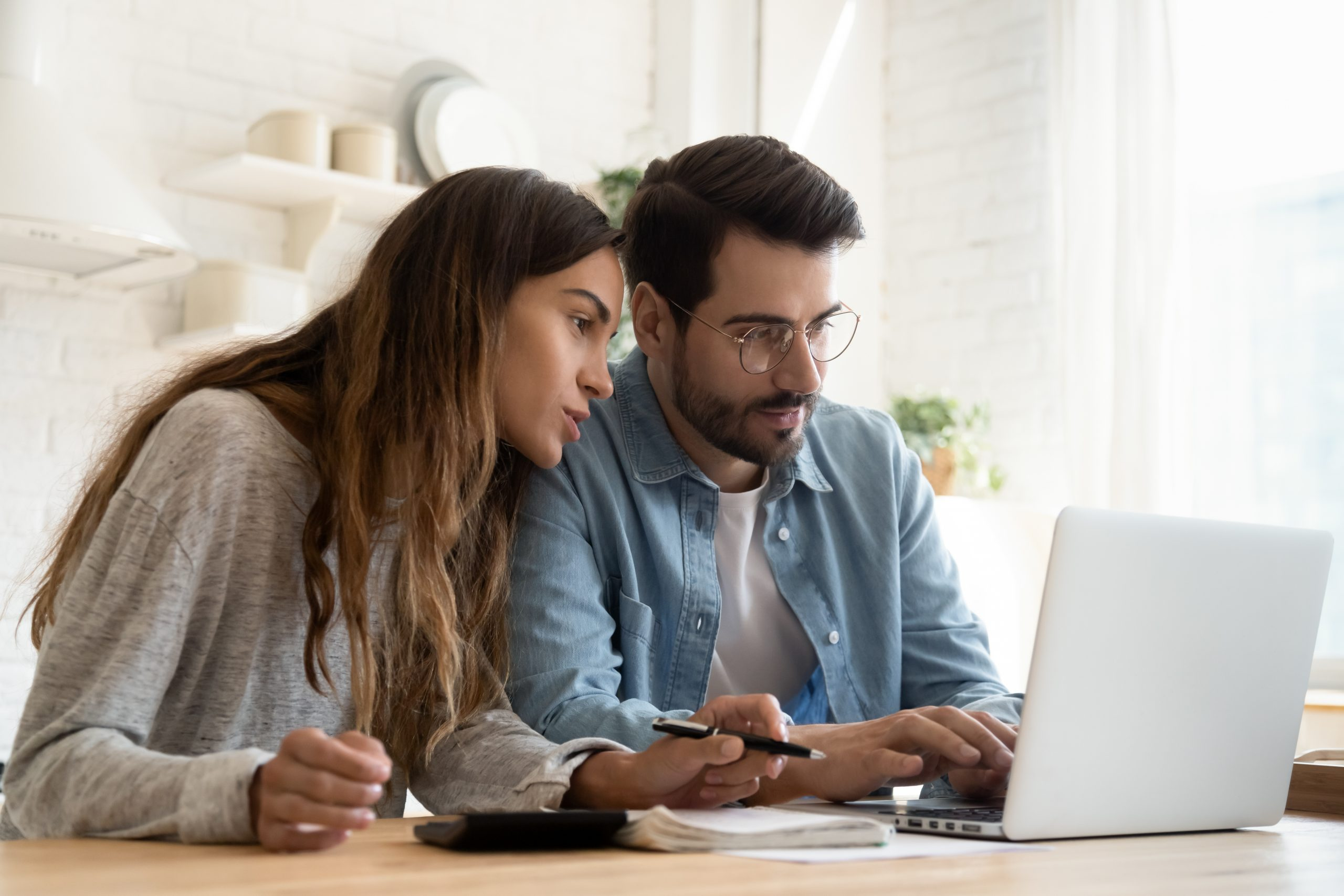 Focused young couple calculating bills, planning budget together
